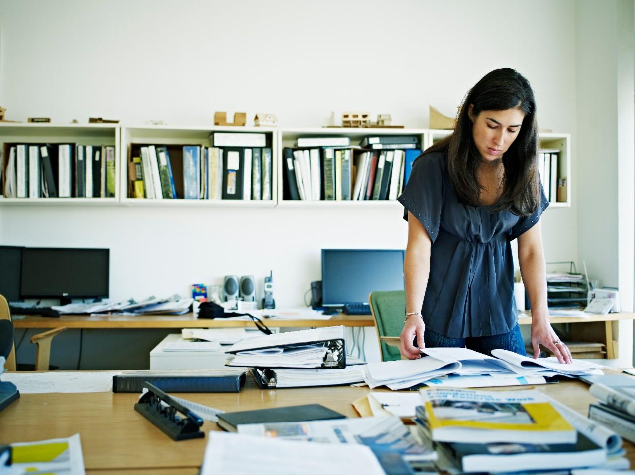 Female architect examining documents at desk